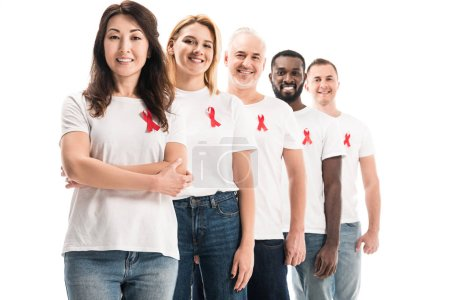 happy group of people in blank white t-shirts standing in row with aids awareness red ribbons isolated on white