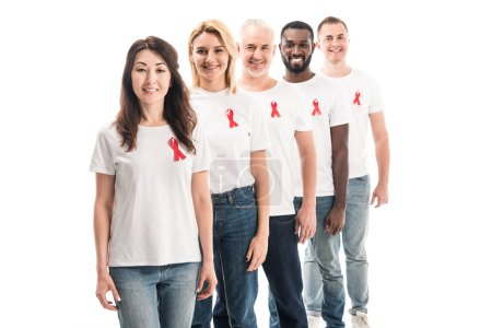 smiling group of people in blank white t-shirts standing in row with aids awareness red ribbons isolated on white