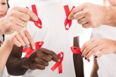 cropped shot of group of people in blank white t-shirts holding aids awareness red ribbons