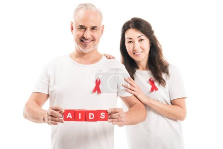 smiling adult interracial couple in blank t-shirts with aids awareness red ribbons and blocks with AIDS lettering looking at camera isolated on white
