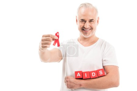 happy mature man in blank white t-shirt with aids awareness red ribbon and blocks with AIDS lettering isolated on white