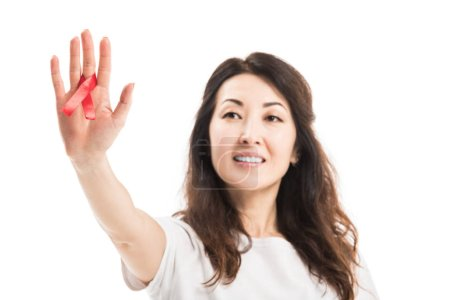 close-up shot of smiling adult asian woman holding aids awareness red ribbon isolated on white