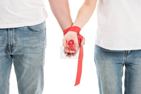 cropped shot of couple holding hands tied with red ribbon isolated on white, aids awareness day concept