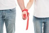photo recadrée de couple main dans la main avec ruban rouge isolé sur blanc, le concept de journée de sensibilisation sida
