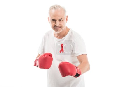 serious mature man in blank white t-shirt with aids awareness red ribbon and boxing gloves isolated on white, fighting aids concept
