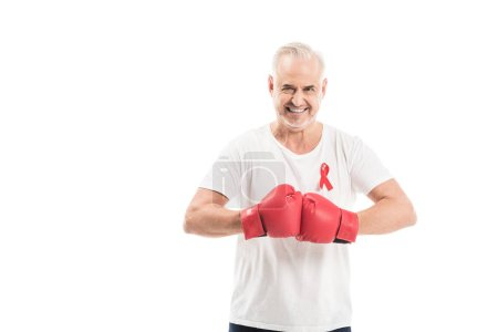 smiling mature man in blank white t-shirt with aids awareness red ribbon and boxing gloves isolated on white, fighting aids concept