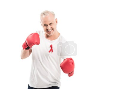 angry mature man in blank white t-shirt with aids awareness red ribbon and boxing gloves isolated on white, fighting aids concept