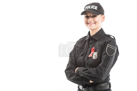 Photo for Happy female police officer with aids awareness red ribbon looking at camera with crossed arms isolated on white - Royalty Free Image