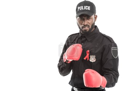 grimacing african american police officer with boxing gloves isolated on white, fighting aids concept