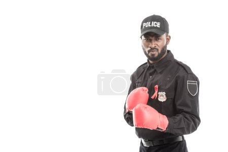 serious african american police officer with boxing gloves isolated on white, fighting aids concept