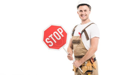 smiling adult builder with aids awareness red ribbon on overall holding stop road sign and looking at camera isolated on white