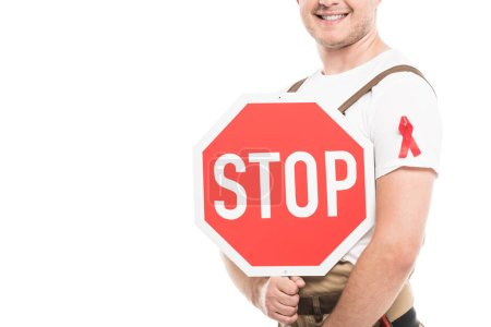 cropped shot of smiling builder with aids awareness red ribbon on overall holding stop road sign isolated on white