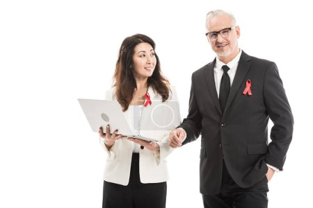 smiling multiethnic adult businesspeople with aids awareness red ribbons working together with laptop isolated on white
