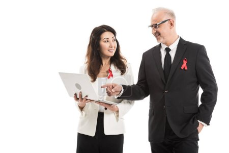 happy multiethnic adult businesspeople with aids awareness red ribbons working together with laptop isolated on white