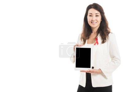 Photo pour Femme d'affaires asiatique souriante avec le ruban rouge de sida sensibilisation sur veste tenant tablet et en regardant la caméra isolé sur blanc - image libre de droit
