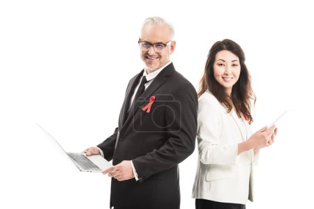 multiethnic happy businesspeople with aids awareness red ribbons working with gadgets while standing back to back and looking at camera isolated on white