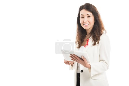 smiling asian businesswoman with aids awareness red ribbon on jacket using tablet and looking at camera isolated on white
