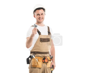 handsome adult builder holding condom and looking at camera isolated on white