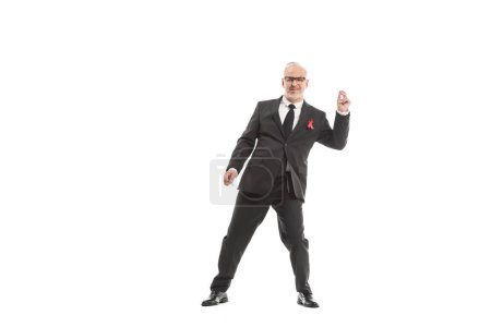 smiling mature businessman in suit with aids awareness red ribbon dancing isolated on white