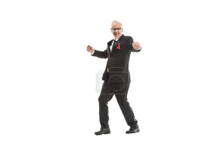 funny mature businessman in suit with aids awareness red ribbon dancing isolated on white