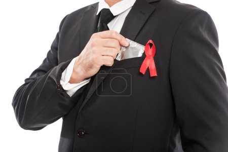 cropped shot of businessman in suit with aids awareness red ribbon holding condom isolated on white
