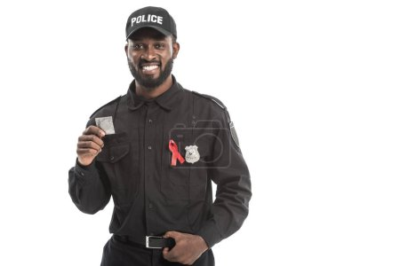 smiling african american police officer with aids awareness red ribbon holding condom isolated on white