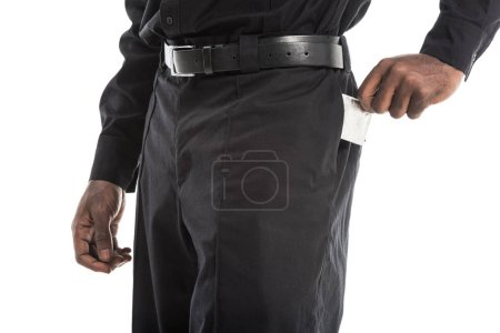 cropped shot of african american policeman taking condom from back pocket of pants, aids awareness concept