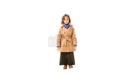 Photo for Beautiful little child in trench coat standing and looking at camera isolated on white - Royalty Free Image