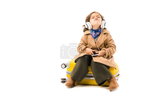 Photo pour Grimaçant petit enfant en trench coat écouter de la musique avec écouteurs et assis sur une valise jaune isolé sur blanc - image libre de droit