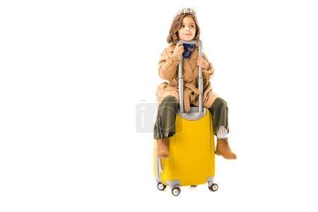 entzückendes kleines Kind im Trenchcoat sitzt auf gelbem Koffer isoliert auf weißem