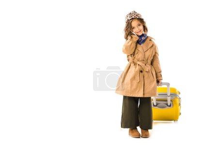 Photo pour Adorable petit enfant en trench coat avec valise jaune parlant par téléphone isolé sur blanc - image libre de droit