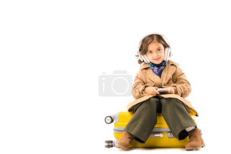 beautiful little child in trench coat listening music with headphones and sitting on yellow suitcase isolated on white