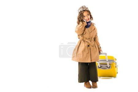Photo pour Heureux petit enfant en trench coat avec valise jaune parlant par téléphone isolé sur blanc - image libre de droit