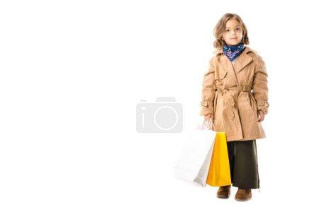 Foto de Adorable niño con estilo en gabardina con bolsas coloridas mirando a cámara aislada en blanco - Imagen libre de derechos