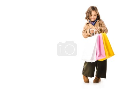 beautiful little child in trench coat holding colorful shopping bags isolated on white