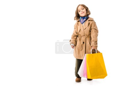 adorable little child in trench coat with colorful shopping bags looking at camera isolated on white