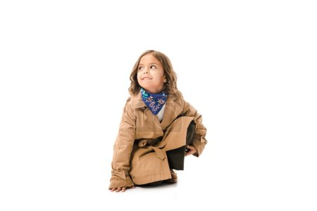 Photo for Stylish little child in trench coat sitting on floor isolated on white - Royalty Free Image