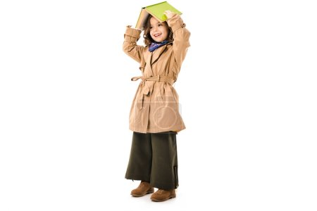 beautiful little child in trench coat covering head with book isolated on white