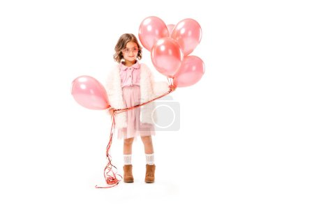 stylish little child in fur coat with pink air balloons isolated on white
