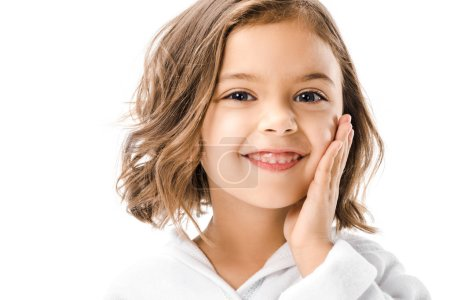 little smiling kid touching face and looking at camera isolated on white