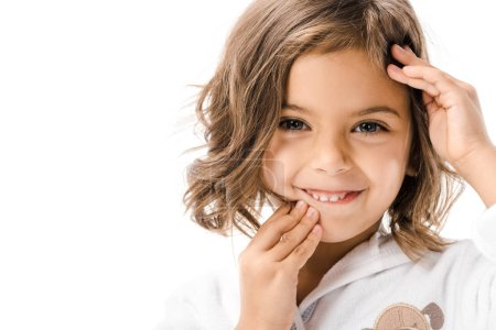 portrait of smiling child touching face and looking at camera isolated on white