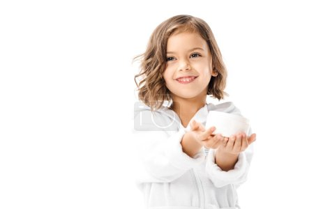 cute kid in white bathrobe showing body cream in hands isolated on white
