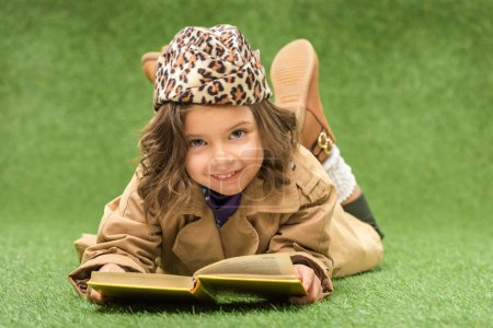 stylish smiling kid with book looking at camera while lying on green grass