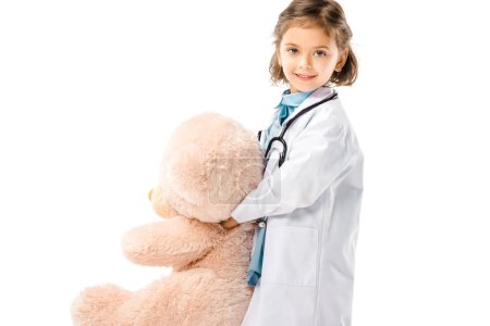 smiling kid dressed in doctors white coat with stethoscope holding big teddy bear isolated on white