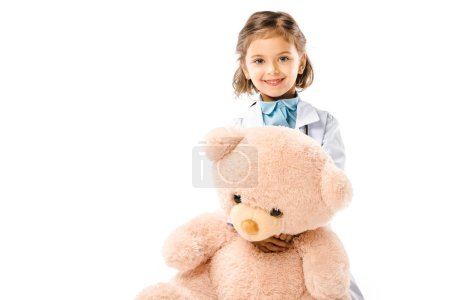 kid dressed in doctors white coat holding big teddy bear isolated on white
