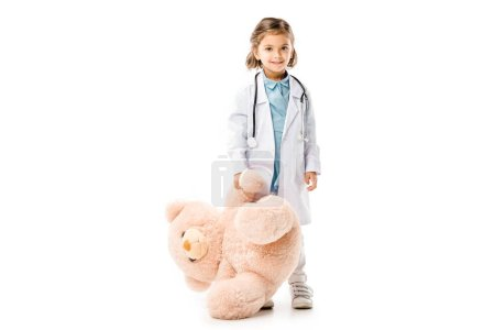 kid dressed in doctors white coat with stethoscope holding big teddy bear isolated on white