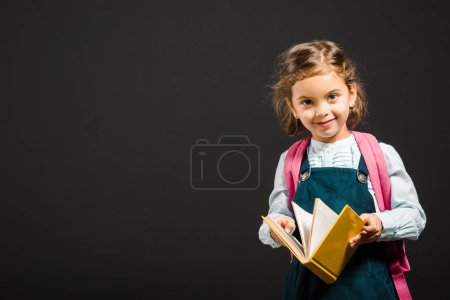 cute schoolgirl with backpack and book in hands looking at camera isolated on black