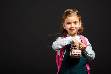 schoolgirl with backpack holding glass jar with savings for education isolated on black