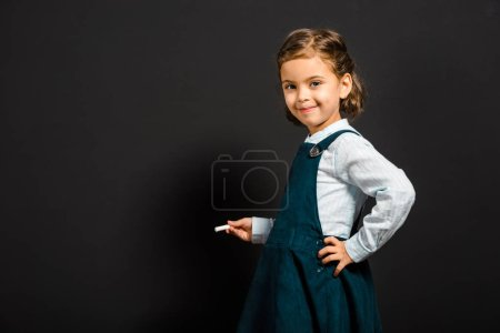 smiling schoolgirl with piece of chalk standing at blank blackboard