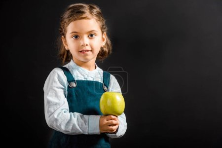 portrait of little schoolgirl with apple in hands looking at camera isolated on black